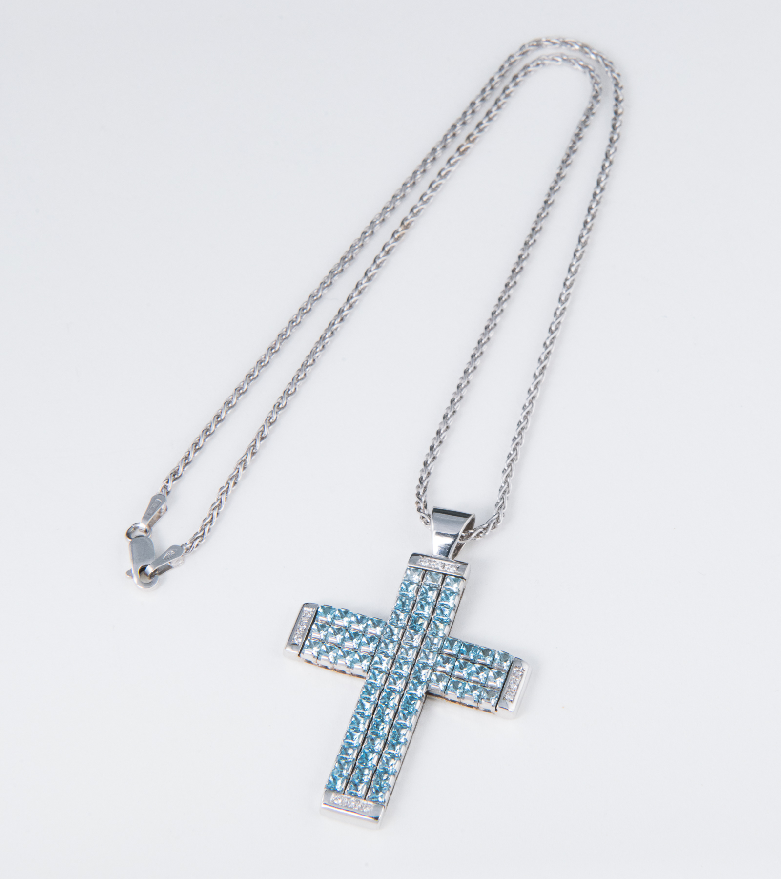 Gargantilla de oro blanco con cruz de topacios azules y diamantes.